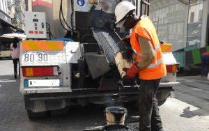 L'ouvrier rempli de goudron des seaux brûlants, servant le revêtement d'étanchéité