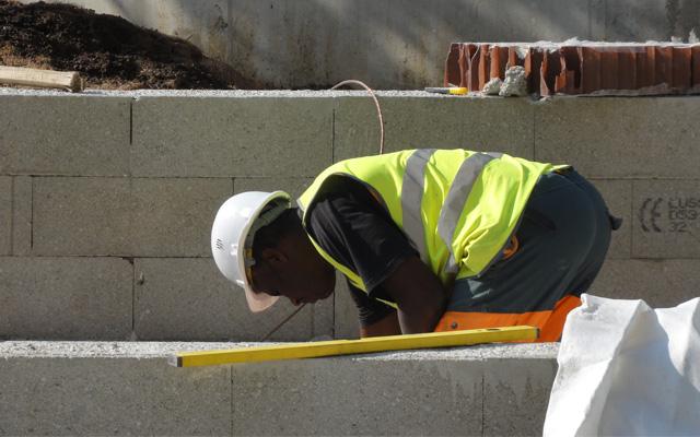 L'ouvrier pose des parpaings avec son niveau