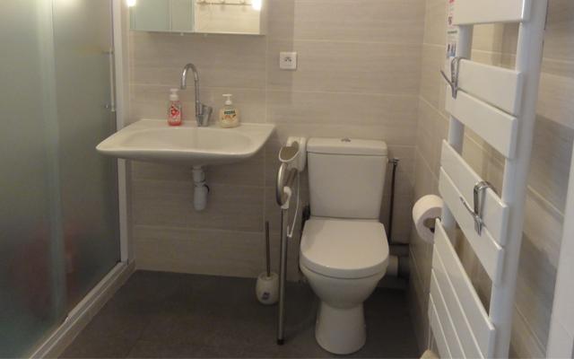 Salle de bain rénovée : le lavabo Handilav, à faible encombrement, facilite l'utilisation d'un fauteuil roulant. La poignée de maintien rabattable sécurise l'accès au WC