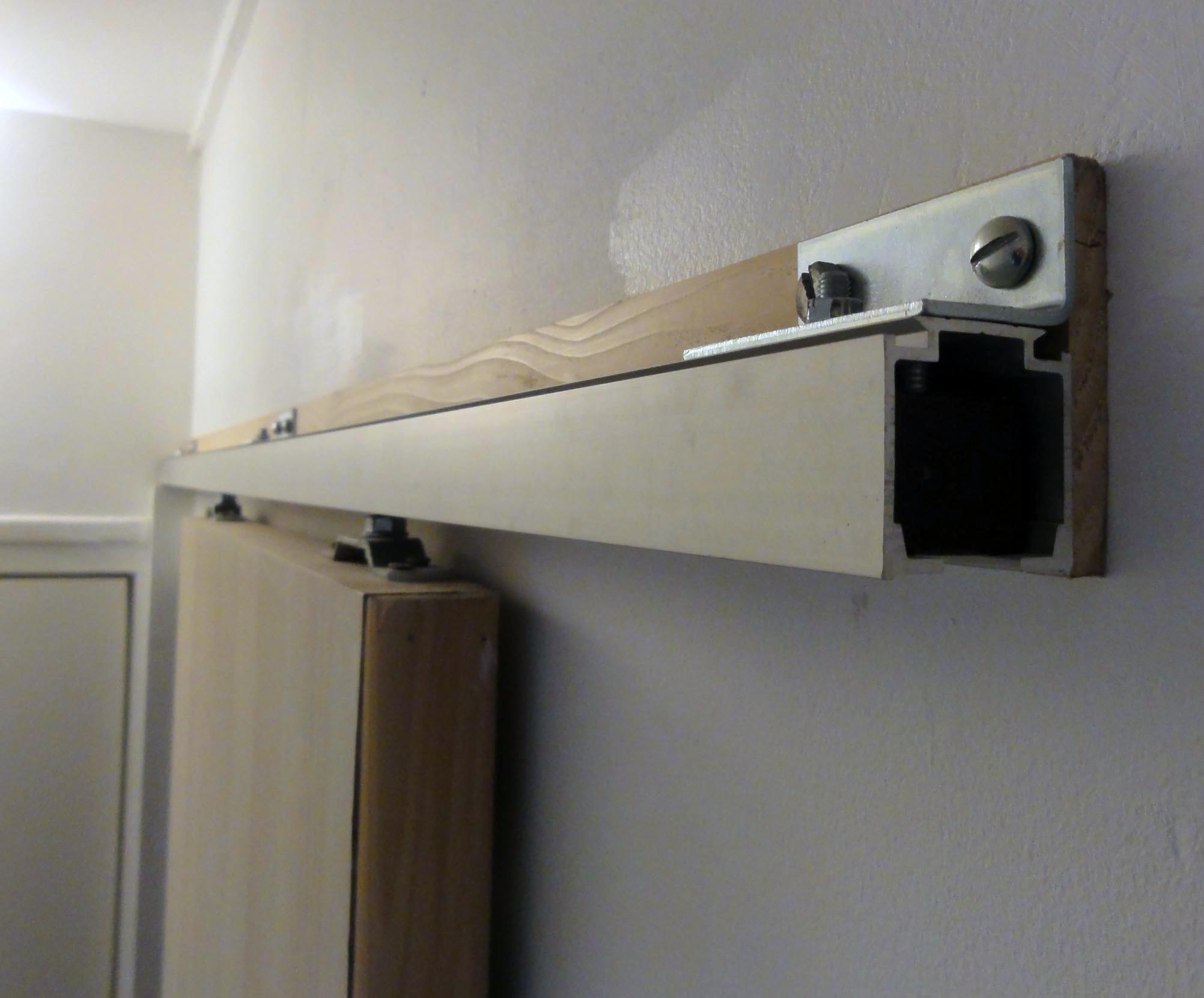 Le tasseau, derrière le rail, permet à la porte de coulisser sans frotter l'encadrement de la porte d'origine