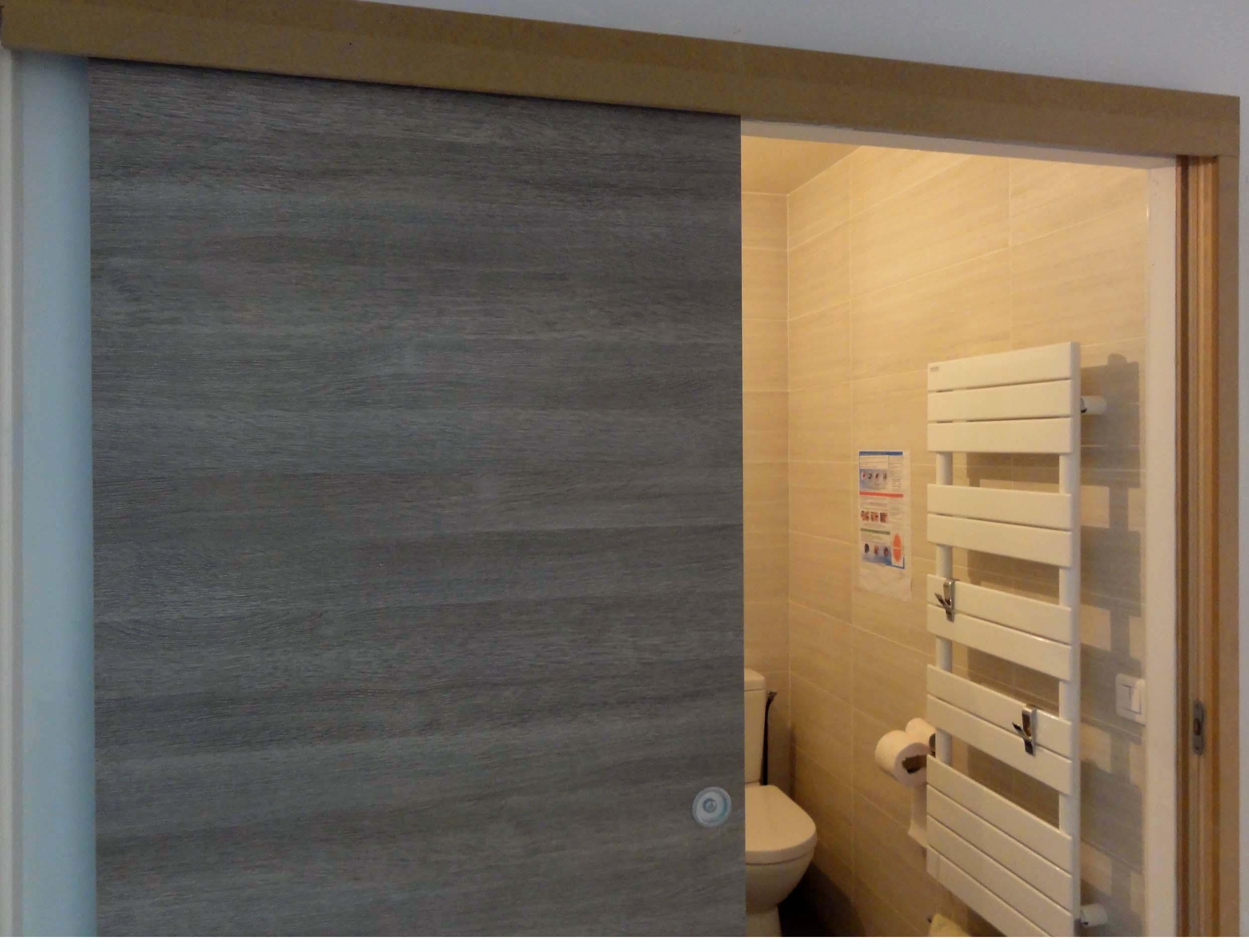 La porte coulissante en applique de 0,83 mètre de large optimise l'accès à la salle de bain