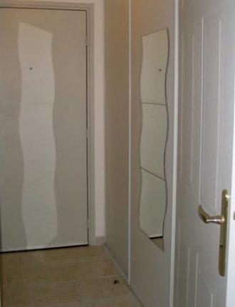 L'entrée cache un dressing à droite, avec un miroir à 3 carreaux