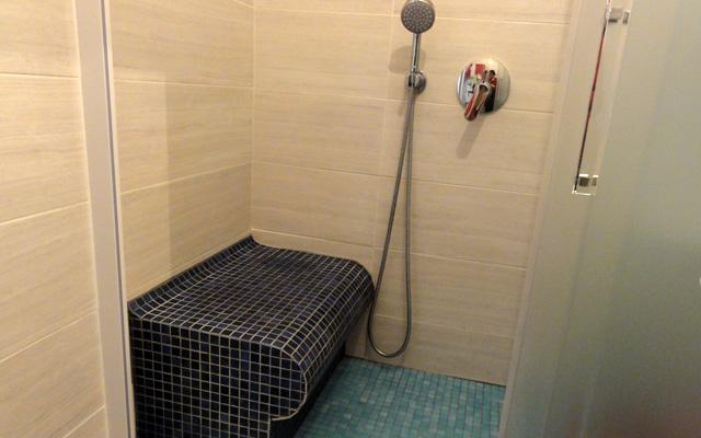 Un banc en Wedi recouvert de mosaïque permet à une personne à mobilité réduite de s'asseoir dans la douche, 80 x 170 cm.