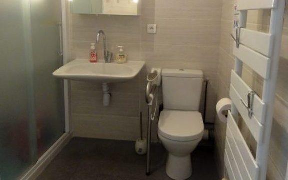 Après les travaux: Le lavabo Handilav, à faible encombrement, facilite l'utilisation d'un fauteuil roulant. La poignée de maintien rabattable sécurise l'accès au WC