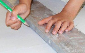 Main trace trait avec un crayon sur la règle