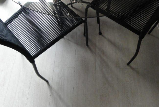Parquet flottant à lame large, gris clair, posé au sol de la salle à manger