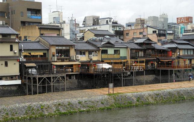 Parmi les maisons modernes citadines, les contructions traditionnelles Machiya (à droite au premier plan) se fondent à Kyoto.