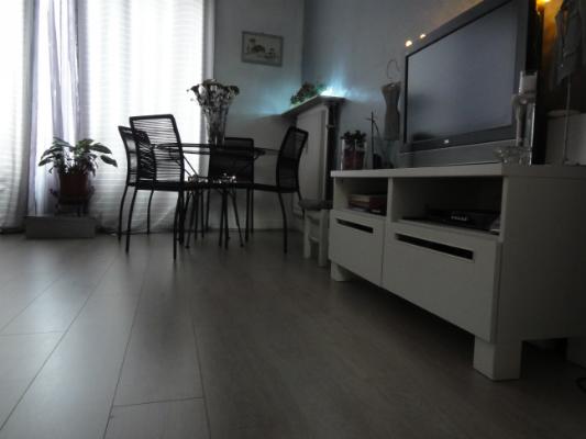 Dans le salon de Maria, un parquet à 4 chanfreins: moderne, à large lame et imitation chêne gris clair