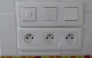 3 interrupteurs de commande posés au-dessus de 3 prises électriques, chez Pierre