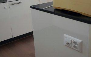 3 prises de courant installées à côté d'un interrupteur, sur le côté de l'ilot central dans une cuisine en Suisse