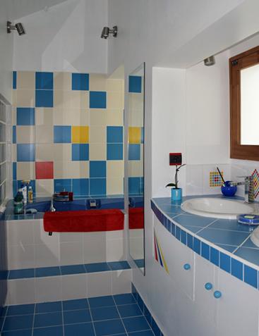 Au dessus de la baignoire: un damier mural en faïence bleue avec des touches rouge et jaune, réalisé par-P-Olivier