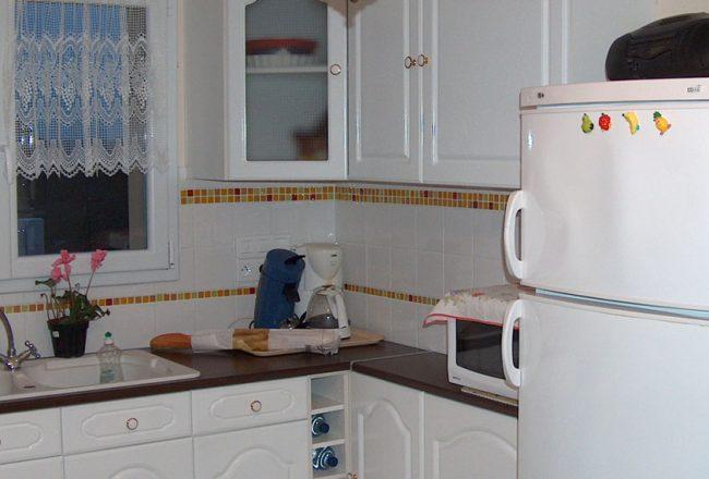 Prises et commandes électriques regroupées dans la cuisine de Pierre