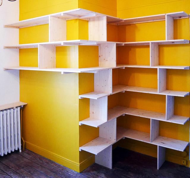 L'ossature de la bibliothèque XXL repose sur un mur jaune moutarde qui renvoie la lumière de la fenêtre (située à gauche)