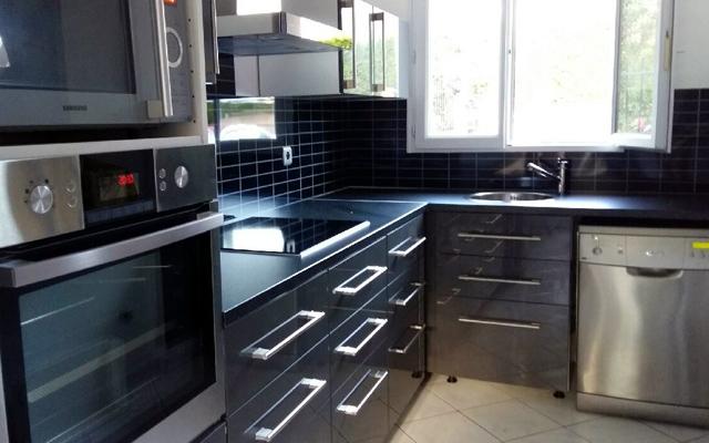 Après: nouveau carrelage noir dans une cuisine moderne, noire et inox