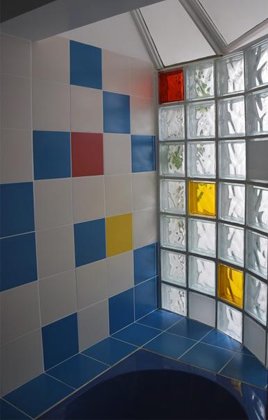 Au dessus de la baignoire, 3è salle de bain créée par P-Olivier: sur un mur, un damier en bleu avec des touches rouge et jaune, et sur l'autre mur, des pavés de verre dans les mêmes tons permettent l'éclairage depuis le puits de jour central.