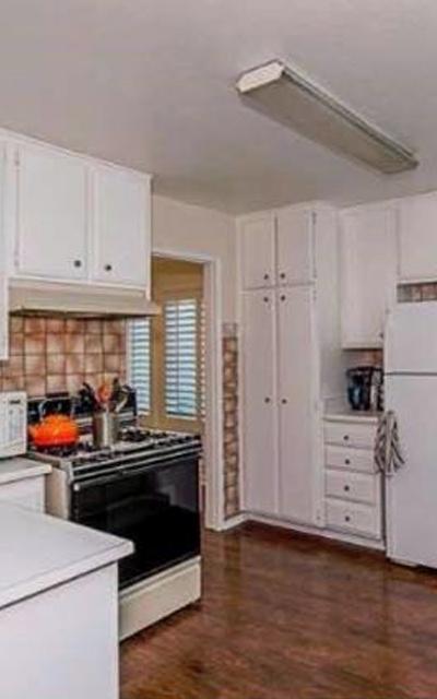 Avant: des carreaux marrons marbrés dans une cuisine blanche