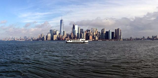 Un ferry mène à la statue de la liberté avec New-York en arrière plan