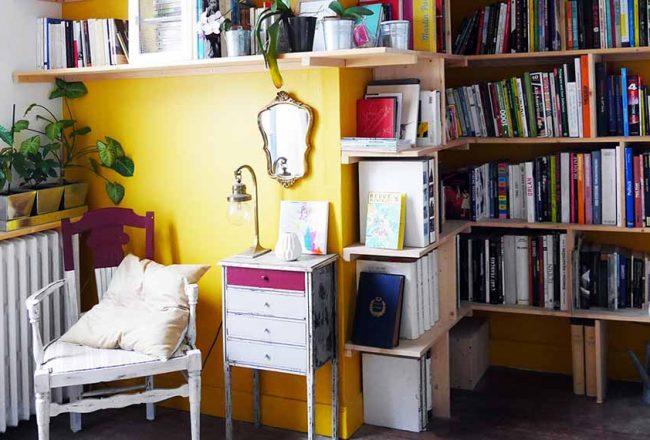 """La bibliothèque d'angle de l'artiste """"Atelier Label Loos"""": aérienne sur un mur jaune moutarde tonique"""