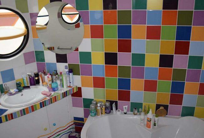 La baignoire d'angle donne sur une mosaïque aux couleurs fruitées de faïence, de Pierre-Olivier