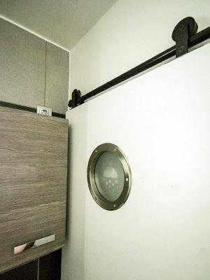 La porte coulisse sur des rails noirs, en applique sur le mur