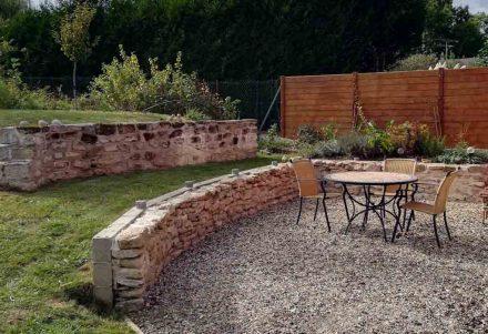 Deux murs en pierres structurent joliment la terrasse et le jardin