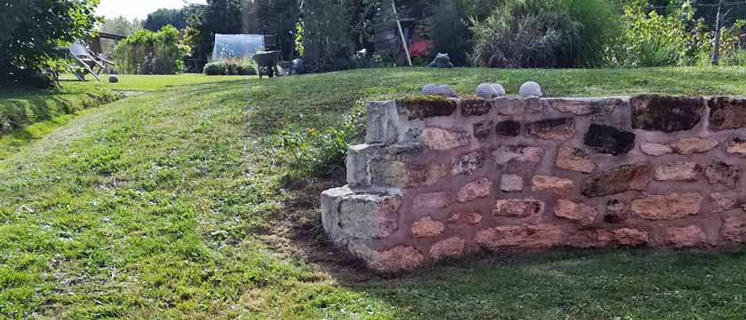 Muret avec 3 niveaux de parpaings sur lesquels sont scellés les pierres.