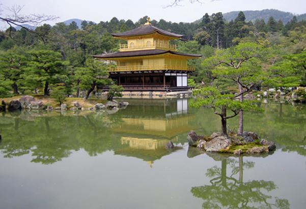 Temple bouddiste à Kyoto: le pavillon d'or de Kinkaku-ji est situé au milieu d'un plan d'eau, entouré d'arbres taillés tels des bonzaïs.